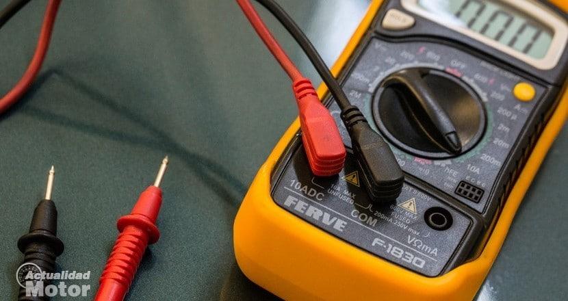 Multímetro para medir el voltaje de una batería de coche descargada