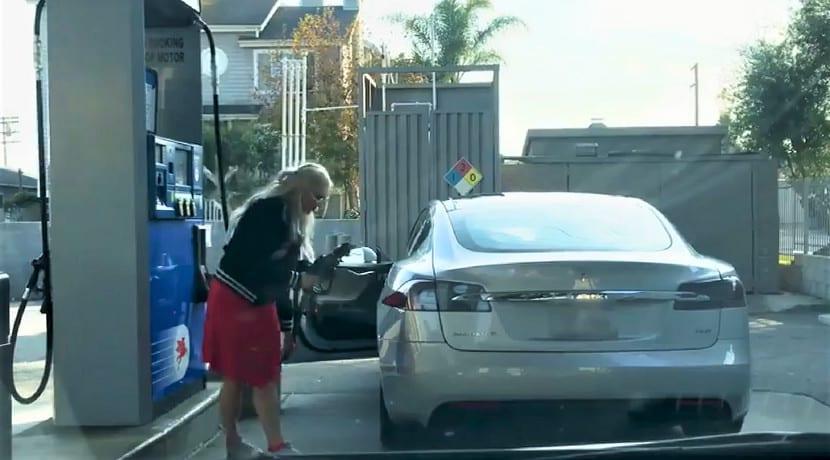 Una mujer intenta llenar un Tesla con gasolina